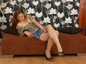 Barbara en jupette en jean, strip sur son canapé