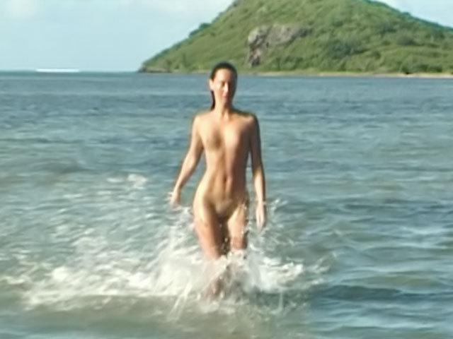 Emmanuelle caresse son corps sur une plage déserte
