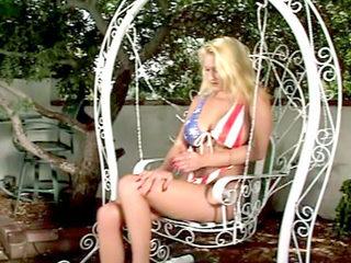 Bionda patriota siliconata si penetra con il dildo nel giardino!
